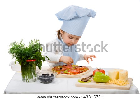 little girl preparing a pizza with cheese and vegetables - stock photo