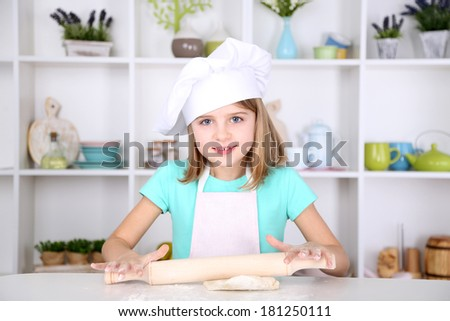 Little girl preparing cake dough in kitchen at home - stock photo