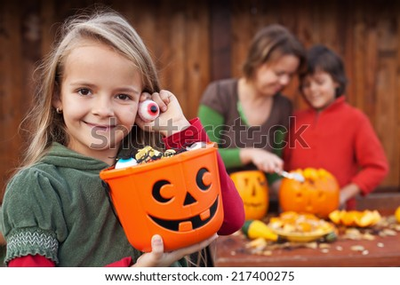 Little girl preparing for the Halloween night with her family - stock photo
