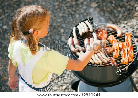 Little girl preparing meat and sausages using a barbecue grill - stock photo