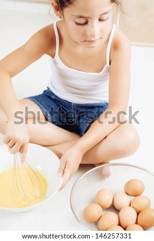 little girl preparing some cake - stock photo