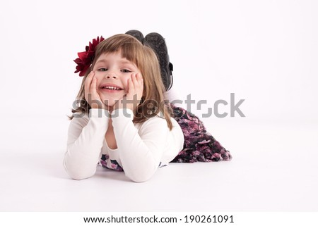 Little girl preschooler model in a flowered skirt with flower in hair lying comfortably on the floor and smiling