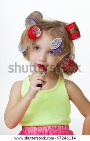 Little girl pretend to be old applying lipstick and wearing hair rollers