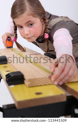 Little girl pretending to be carpenter - stock photo