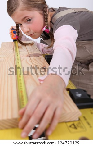 Little girl pretending to be carpenter - stock photo