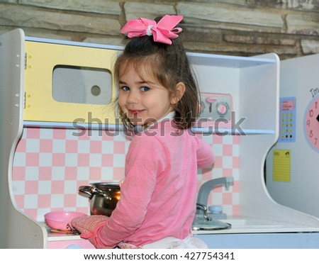 Little girl pretends to be the mom cooking diner for her family.  She is wearing a pink shirt and bow.  She is standing by her stove, with pot holder on her hand, stirring her pot.
