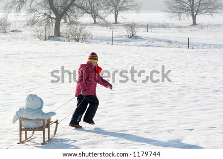 Little girl pulling a baby in sled - stock photo