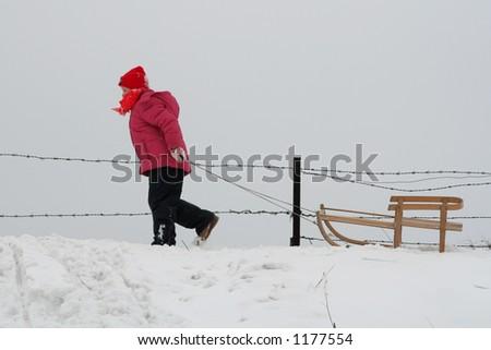 Little girl pulling her sled - stock photo