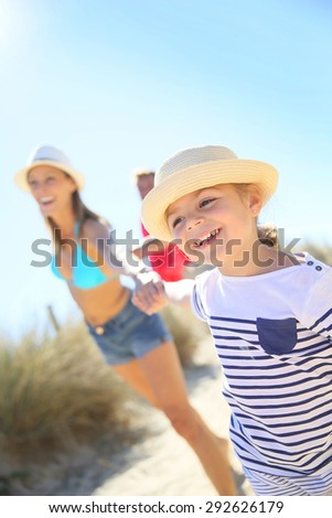 Little girl pulling parents' arms to run to the beach - stock photo