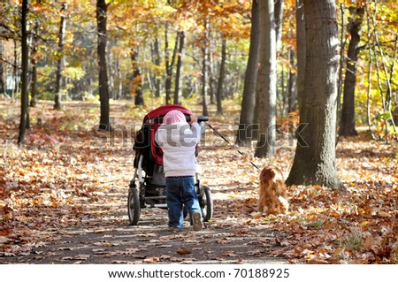Little girl pushing pram and dog leads