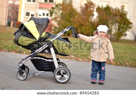 little girl pushing stroller with her sister
