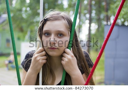 Little girl put her head among coloured horizontal bars - stock photo