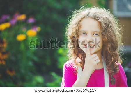 little girl putting finger up to lips and ask silence. Toning photo. - stock photo