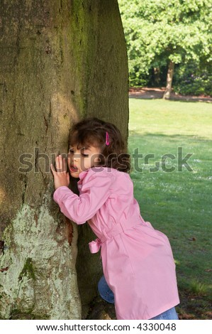 Little girl putting her ear against a large tree, listening to the gnomes