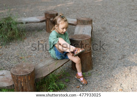 Little girl putting her sandal on