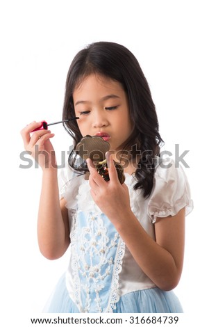 Little girl putting on make up on her face.