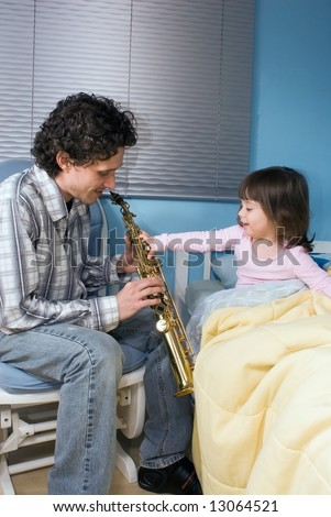 Little girl reaching out to grab her father's saxophone while he plays her a lullaby - stock photo