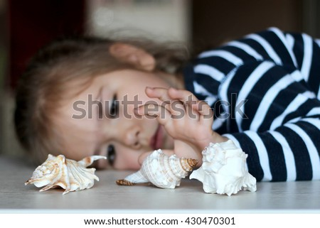 Little girl reaching the sea shell, selective focus, focus on the central shell, dream about summer vacation - stock photo