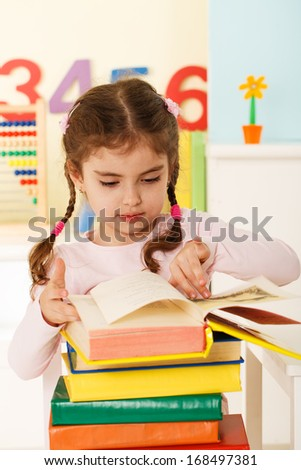 Little girl read many books - stock photo