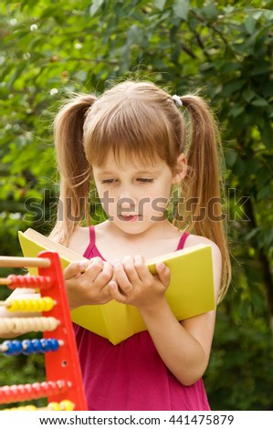 little girl reading a book. child boring to read