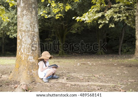 Little girl reading a book in the shade of a tree