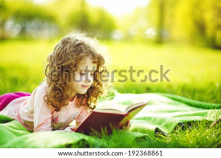 Little girl reading a book in the spring park, toning photo. - stock photo
