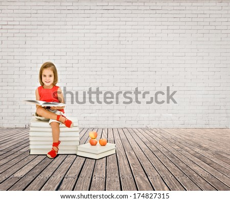 little girl reading a book on a room with white bricks wall and wood floor - stock photo