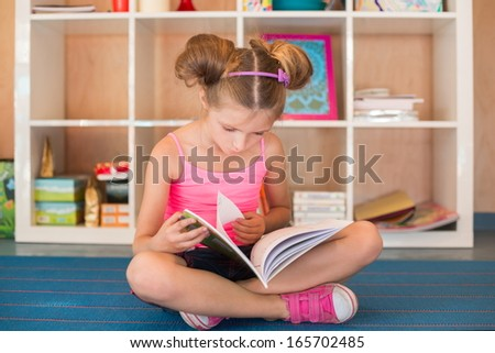 Little girl reading a book on the floor playground - stock photo