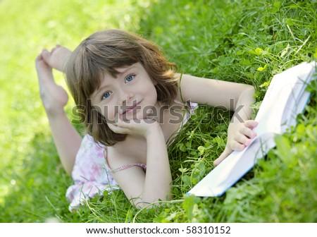 Little girl reading a book outdoor - stock photo
