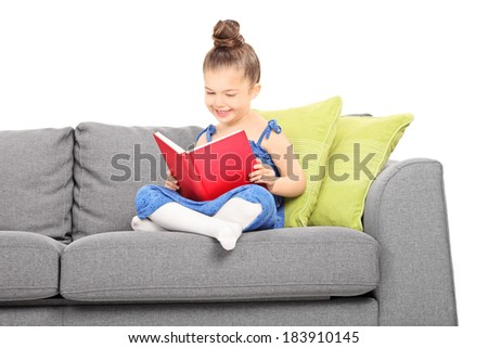 Little girl reading a book seated on sofa isolated on white background - stock photo
