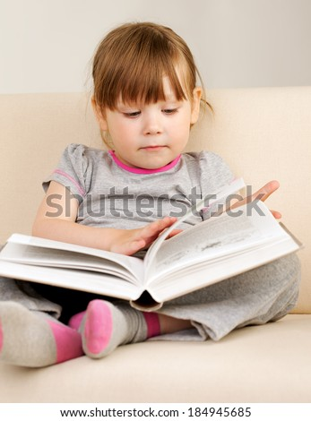 Little girl reading a book sitting on the couch - stock photo