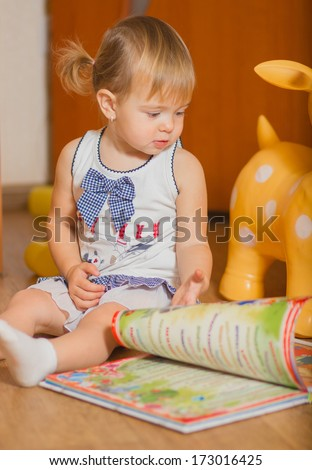 little girl reading a book sitting on the floor
