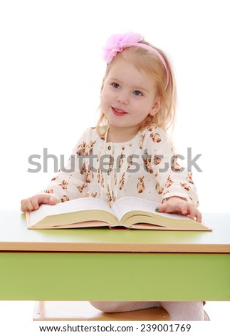Little girl reading a book while sitting at the table. Studio photo, isolated on white background. - stock photo