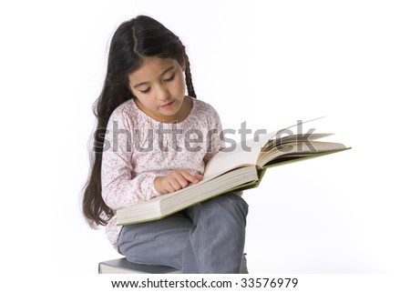 Little girl reading a large book