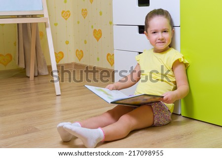 Little girl reading book at home (book are unrecognizable) - stock photo