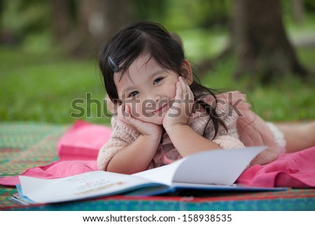 Little girl reading book in the garden