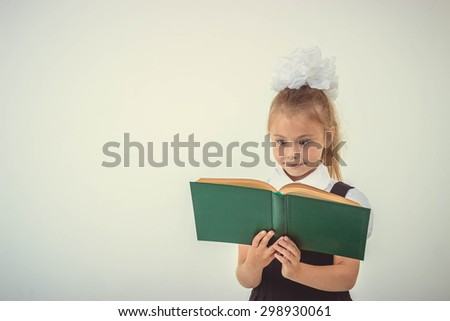 Little girl reading book, preparing for school, isolated - stock photo