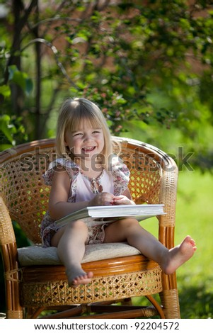 Little girl reading book sitting in wicker chair outdoor in summer day - stock photo