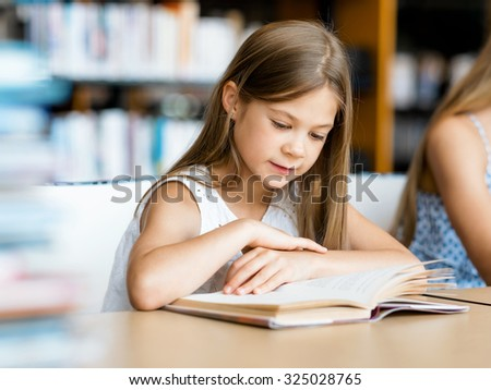 Little girl reading books in library - stock photo