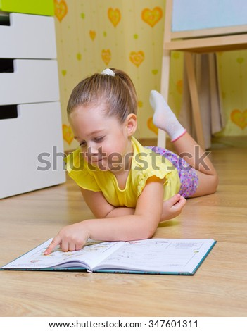 Little girl reading box in a home (book are unrecognizable) - stock photo