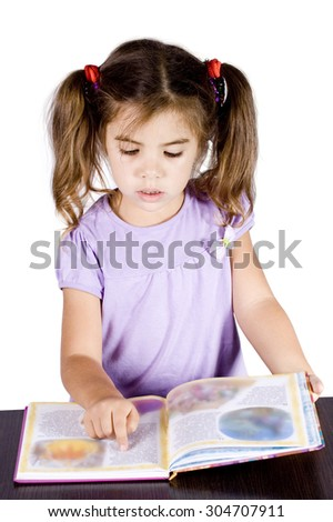 little girl reading brilliant book of fairy tales at the desk - stock photo