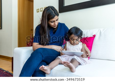 Little girl reading e book on tablet with her mother - stock photo