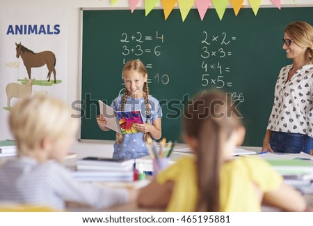 Little girl reading homework in the classroom