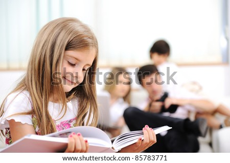 Little girl reading in home, indoor with happy family - stock photo