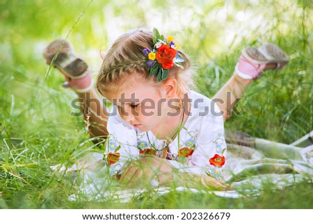 Little girl reading tales lying in green grass - stock photo