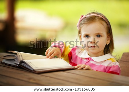 little girl reads a book