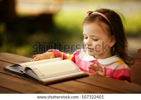 little girl reads book - stock photo