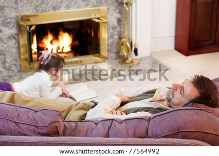 Little girl reads by the fire while Dad naps - stock photo