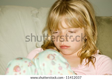 Little girl ready for bed looking sleepy or ill or sad - stock photo