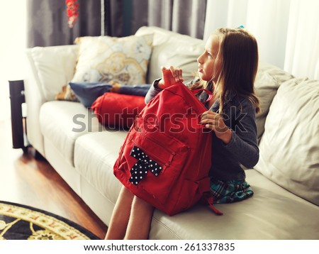 little girl ready for school at home with school bag. - stock photo